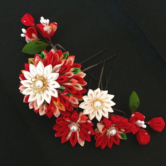 つまみ細工で作りました繊細で可憐な雰囲気の髪飾りです。大きな造花のような華やかさは少ないですが、作りが細かく上品です。まるまるとした半くすの形のお花と二種類のお花のつぼみがポイントとなり、可愛いです。上品で、ちょっとレトロな雰囲気の髪飾りをお探しの方にい...