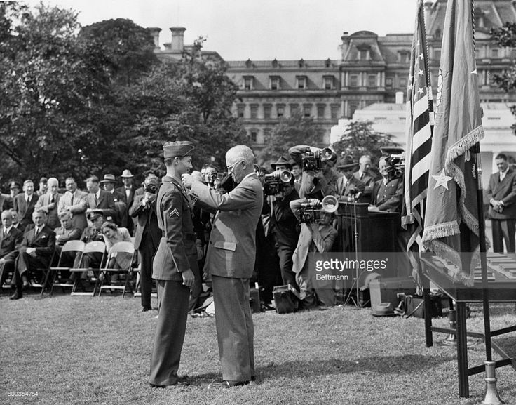Among the fifteen servicemen awarded the Congressional Medal of Honor at a mass presentation in the White House gardens was Corporal Desmond T. Doss, Lynchburg, VA, shown receiving the Nation's top award from President Harry S. Truman. Corporal Doss, the only conscientious objector ever to receive the award, earned the citation while serving as medical corpsman with the 77th Division on Okinawa.