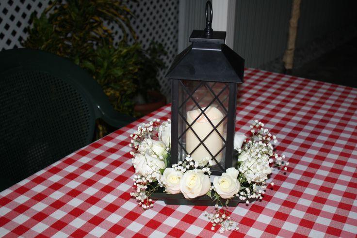 Centro de mesa con un farol y flores naturales.