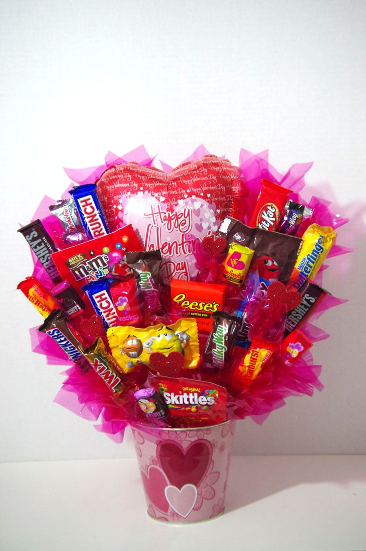 A handmade arrangement of your favorite candy in a pink heart tin. A great gift for Valentine's Day . Arrangement contains a mix of candy including Kit Kat, Skittles, Twix, Variety of M&Ms, Almond Joy