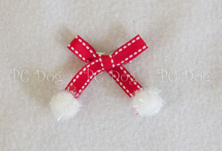 "This beautiful hair bow has red ribbon, with cute white pom poms on the bottom of each ribbon tail. It measures approximately 2"" by 2', and attaches to the hair with an alligator clip."