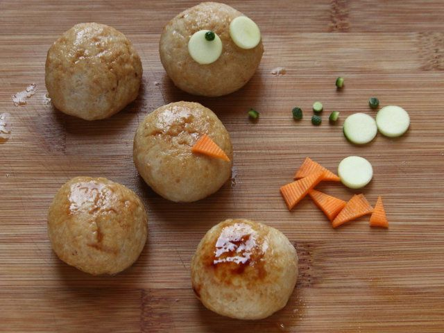 """POLPETTE NEL """"NIDO"""" 5/5 - Ricavate dei dischetti dalle fette di zucchine (più grandi nella parte chiara e più piccoli nella parte della buccia) e dividete le fette di carota a triangolini. Formare, quindi, con le verdure una faccina sopra ogni polpetta. Condite le strisce di zucchine e carote con l'olio rimasto. Sopra ogni singolo piatto distribuite le verdure a forma di """"nido"""", ponetevi al centro le polpette e, dopo aver diviso il sedano a metà, disponetelo sui 2 lati del nido."""