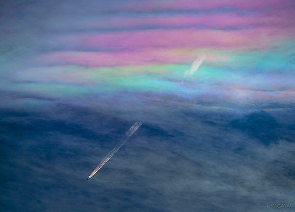 彩雲をくぐった飛行機の虹色の飛行機雲がTwitterに投稿され、大きな反響を呼んでいる。この写真は、映像作家のKAGAYAさんが山梨県忍野村の標高1000メートルの場所から超望遠レンズを使用して撮影したもの。日光が雲