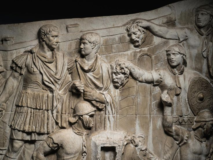 Picture of a scene in the column where two Roman auxiliaries present Trajan with severed enemy heads