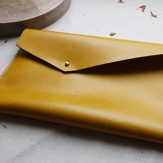 Eye catching simple asymmetric clutch bag. This clutch is lovingly hand dyed to a deep yellow colouring and hand sewn with a contrasting white linen thread using a saddle stitch, hand stitching is arguably stronger than a machine stitch, meaning that you can love your bag for even