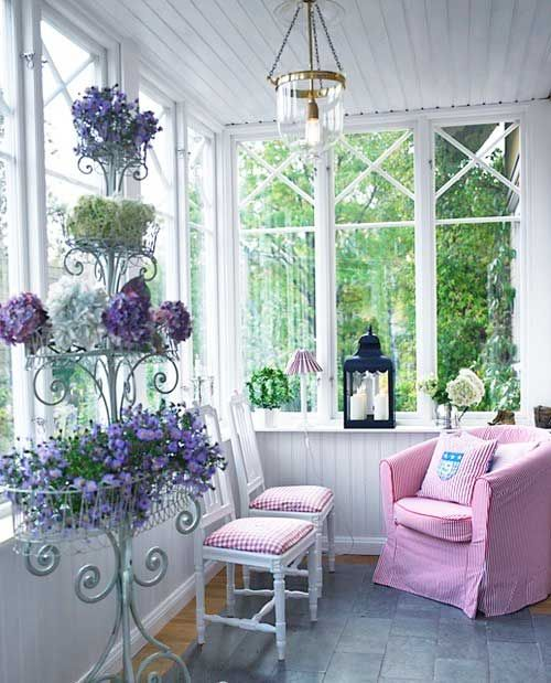 This is a more sophisticated look for a pink-themed porch.  The dark blue lantern and hydrangeas on this cute stand sets this space for reading a good book.