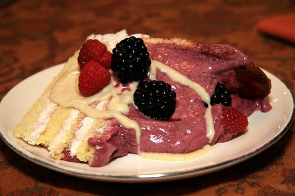 Wild Blackberry Bavarian Cream Mousse: A 4-layer Italian Genoese Sponge Cake layered with Wild Blackberry Heirloom Frosting, surrounded by a double-high fence of homemade Ladyfingers that is filled with Wild Blackberry Bavarian Cream, dotted on top with fresh berries, oh, and drizzled with Creme Anglaise (Vanilla Custard Sauce).