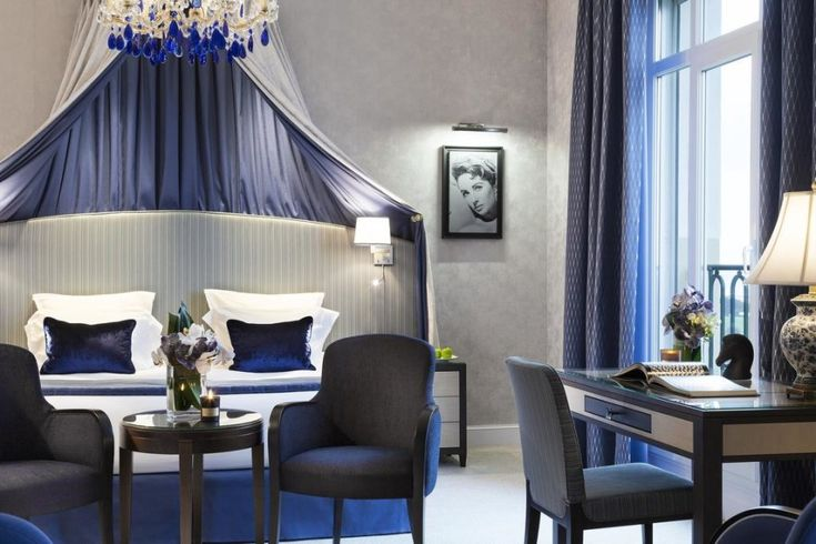 Luma chairs in Navy Blue from Sandler Seating. Upholstered chairs with a solid wood frame at a bedroom in Hotel Barriere L'Hermitage, France.