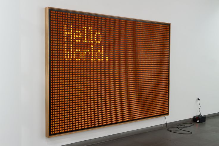 "ello World by Valentin Ruhry, composed of scores of illuminated rocker switches, speaks to both an interest in technology and the visual language of Minimalism. The switches turn on and off representing the simplicity of the technology and the binary number system's two-binary digits 0 and 1. The illuminated message is a nod to the ""Hello World"" computer program, one of the earliest programs that prints out ""Hello World"" on the computer screen. The piece creates a dialogue between the…"