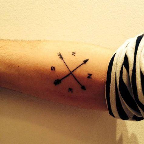 Tatuaje de una brújula que incluye dos flechas cruzadas en el antebrazo de Marcel.