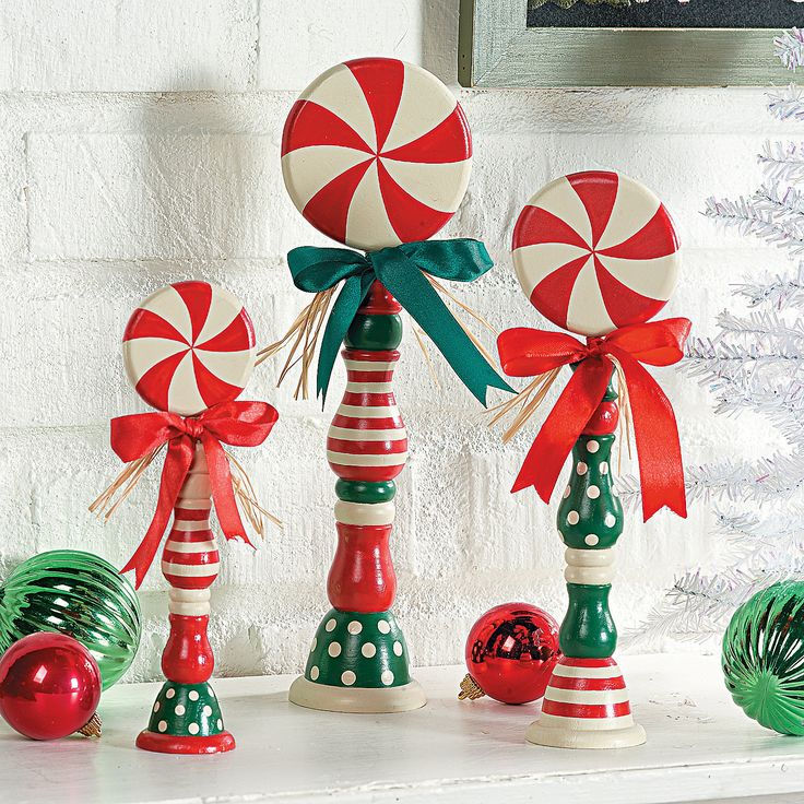 "These Candy Spindles are vibrant Christmas decorations for your holiday season! Candy Spindles have the look of large red and white striped peppermint candies atop stands with an assortment of green, white and red designs. They make great Christmas accents to the dinner table, end tables or any place else you'd like to spruce up. Painted and decorated with ribbon and raffia. Wooden. (3 pcs. per unit) 8"" to 12""H. © OTC"