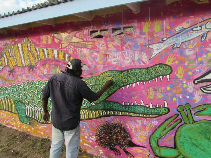 "Elliot Koonutta paints a crocodile as part of the Art Centre Mural project. Our art is a bridge between our culture, community and the outside world. Pormpuraaw means ""entrance way to a house"" in Kuuk Thaayorre language. We are an aboriginal community strong in language and culture. It is a beautiful place surrounded by wetlands next to the sea of  Carpentaria on the Cape York Peninsula Queensland Australia. The Centre is dedicated to assisting community artist and cultural maintenance."