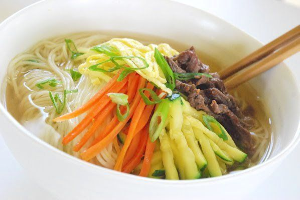 """Janchi guksu, translated into """"banquet/feast noodles,"""" is a simple warm noodle dish made with thin wheat flour noodles (somyeon) that are usually in a clear anchovy or beef broth. It is typically topped with thin strips of beef, eggs, and vegetables. The most common vegetable used for this noodle dish is zucchini. This warm noodle …"""
