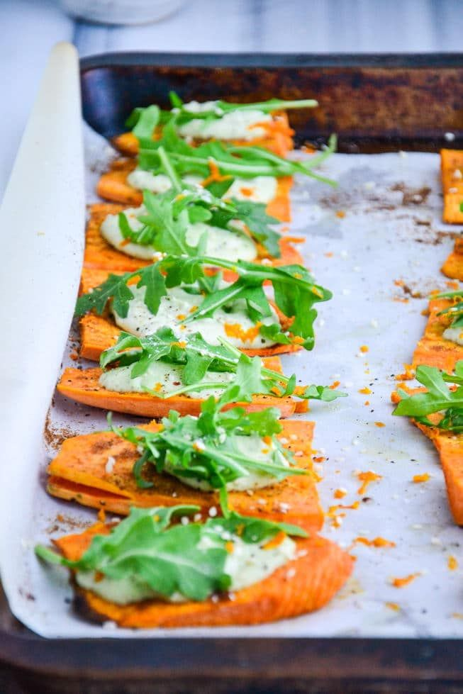 Sweet Potato Appetizer Bites hot out of the oven with arugula on top.