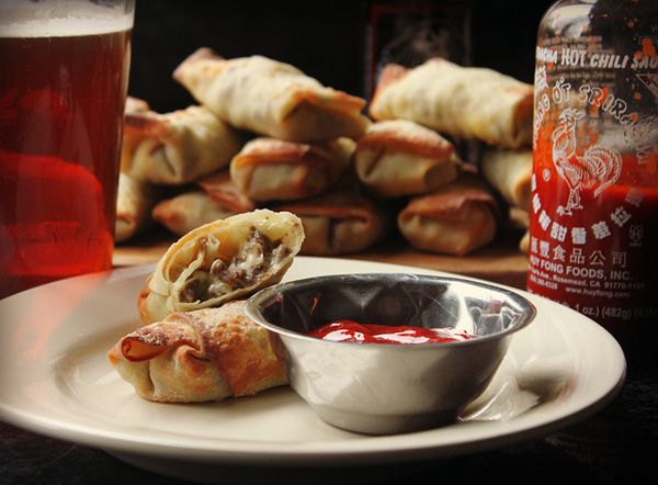 Cheesesteak Eggrolls with Sriracha ketchup - Warning: Make a tray of these once... and you'll be asked to make them over and over again!
