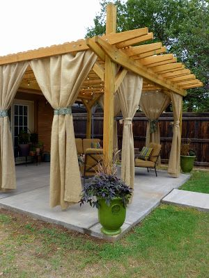 Backyard inspiration: open pergola, white string lights, comfy fabrics, and burlap drapes