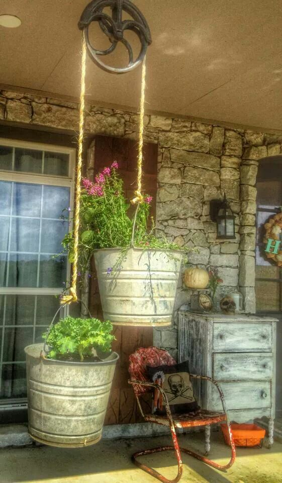 cast iron pulley with buckets as pot holders for flowering plants                                                                                                                                                      More