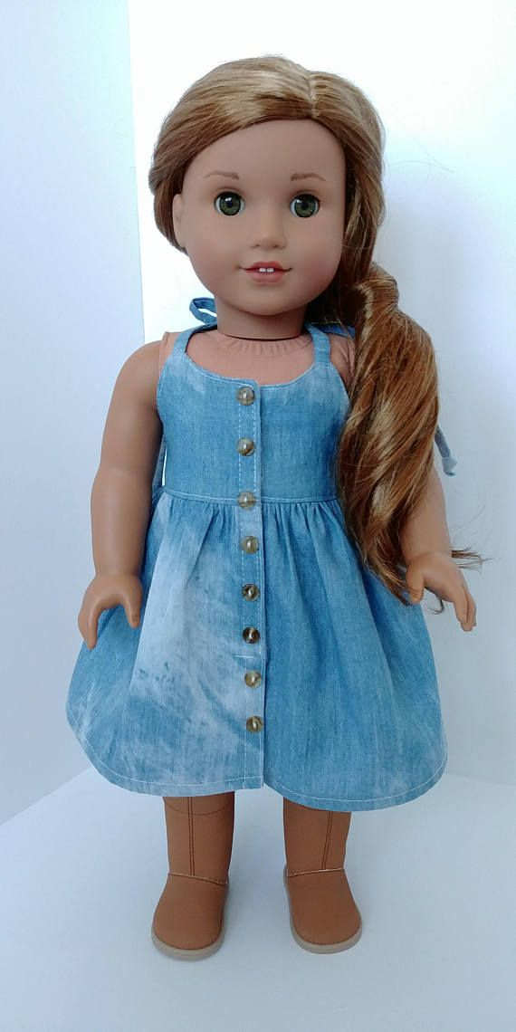 Handmade cotton jean dress. Fits 18 inch dolls. Dress is denim with button details. Velcro closure. The back has a pretty tie ifeature which allows you to tighten the straps..Gathered waistline with topstitching. Used Forever 18 inches pattern. Boots not included. in the area: