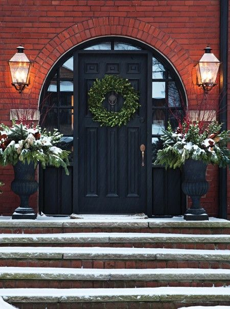 Christmas Decorating: Beautiful black door with arched red brick entry, a simple wreath and greenery filled urns ...