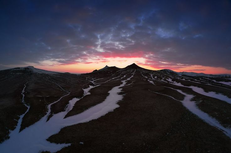 """The Sun sets down after the """"peaks"""" of the Muddy Volcanoes. The silence is absolute, not even a bird in the air, but, during the day, the wind squeezed the fluffy snow into the ravines carved by water."""