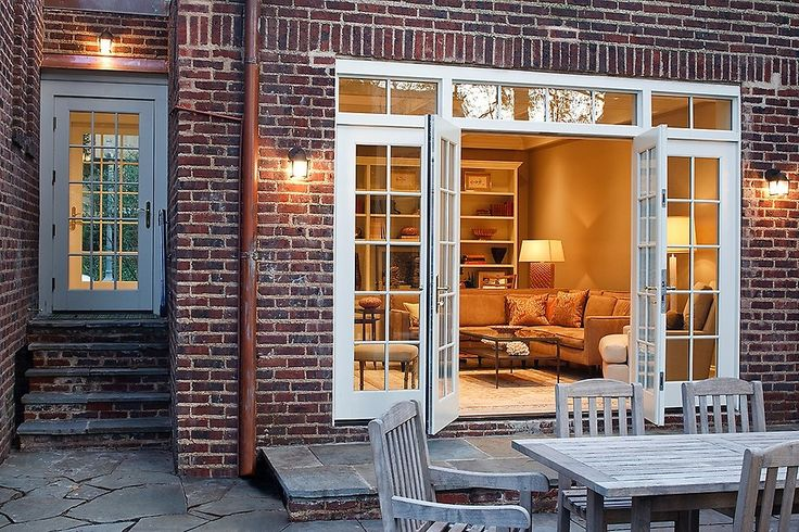 What a beautiful back patio! Love the french doors that open up to the patio ♥ Click this pin to see the full-wall bookshelf in this home