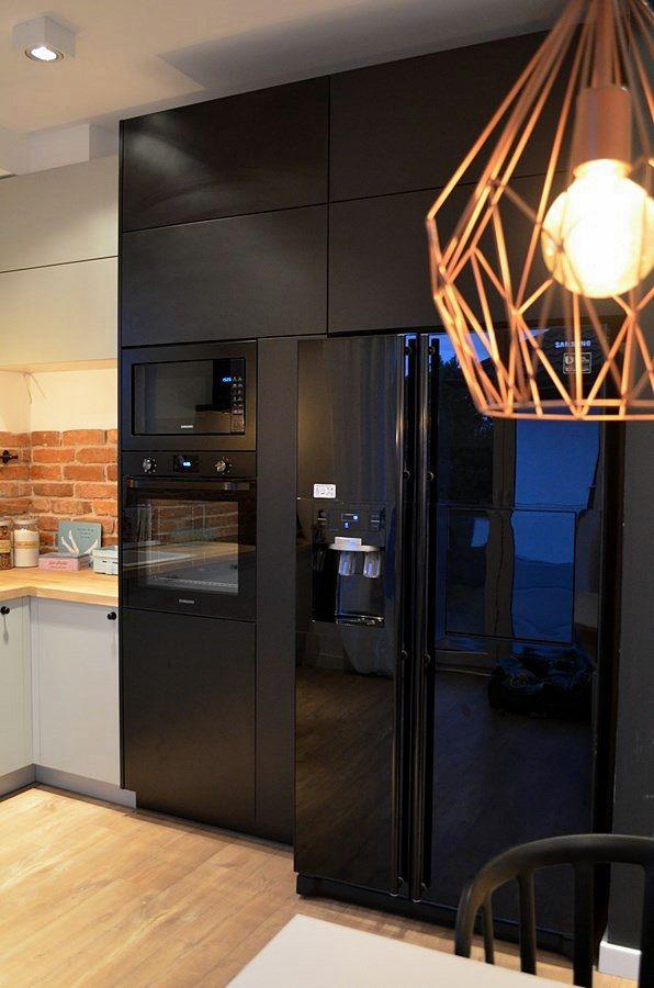 Czarna zabudowa kuchenna i czarna lodówka w kuchni