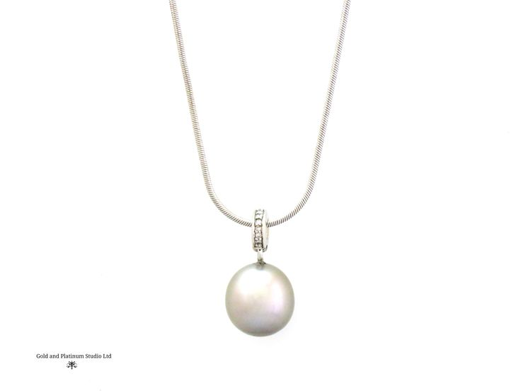 A stunning Tahitian silvery grey pearl, set with diamonds in the bale. A very elegant piece.
