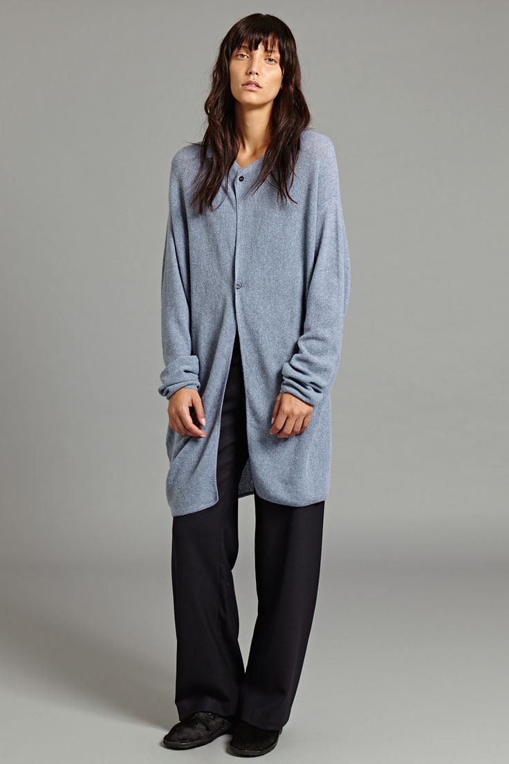 Nilo Cashmere Cardigan In Ice Grey.  This knitted cashmere cardigan features a subtly draped construction that creates a silhouette both distinctive and understated. It fastens with two buttons at the chest and neckline for serene and free-flowing movement.