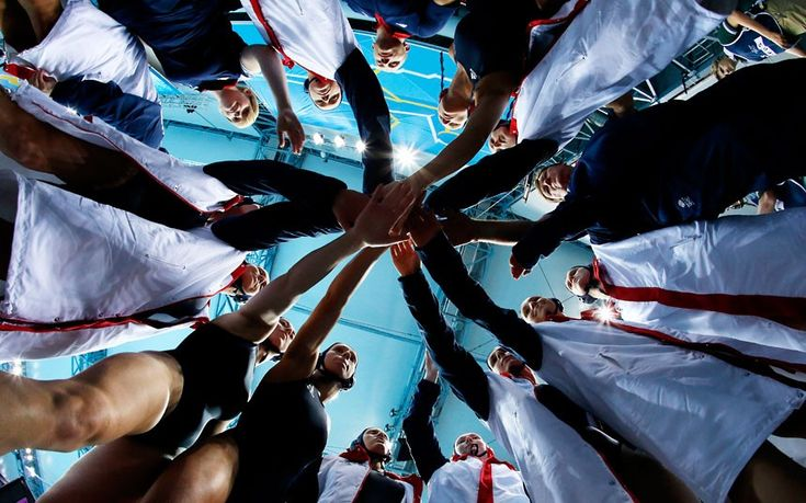 Britain women's water polo players touch hands before an Olympic match