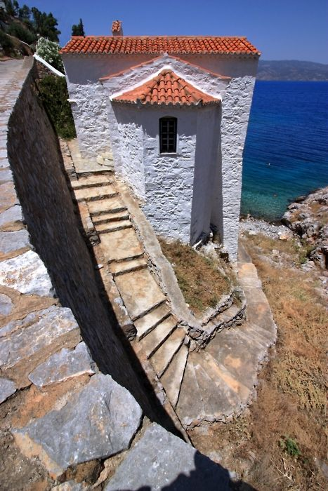 Red-tiled roof church and steep stone staircase overlooking the sea. Mandraki ~ Hydra island, Greece