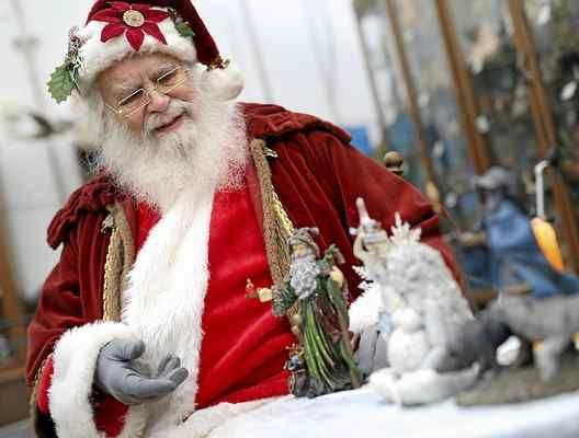 Oberon Zell gestures to statues depicting Santa Claus from various cultures at the Academy of Arcana in Santa Cruz on Sunday. Zell was reading stories as part of the Winter Wonderland celebration, a fundraiser for the academy's museum. (Kevin Johnson -- Santa Cruz Sentinel)