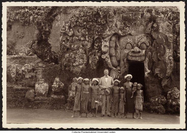 Europese man met aantal Indonesische kinderen voor (tempel?)gebouw