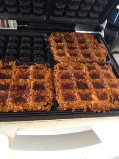 Heat the waffle iron to its medium setting. Meanwhile, peel the uncooked sweet potatoes (or yams) and grate them on the large holes of a box...