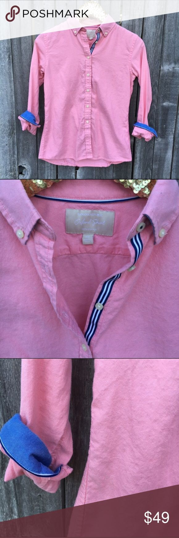 """{banana republic} Light Red Button Down Oxford XS EUC! Like new! Beautiful red Oxford. Appears light red or salmon in color. Fun Navy & White ribbon detail down inside of buttons and blue with navy cuffs for chic flare. Classic, casual or dressy. All American Woman! 🇺🇸 17"""" pit to pit, 25"""" shoulder to hem length, 23"""" sleeves. 100% Cotton. Offers warmly welcomed! Banana Republic Tops Button Down Shirts"""