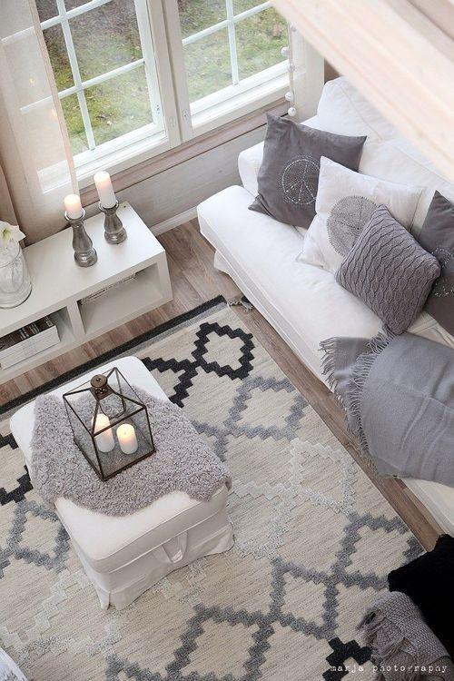 sala de estar decorada com tapete cinza, preto e beje, sofá branco aom almofadas em cinza