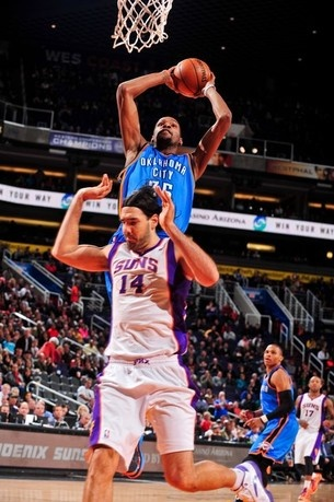 Kevin Durant of the Oklahoma City Thunder rises for a dunk against Luis Scola of the Phoenix Suns on January 14, 2013 in Phoenix, Arizona.