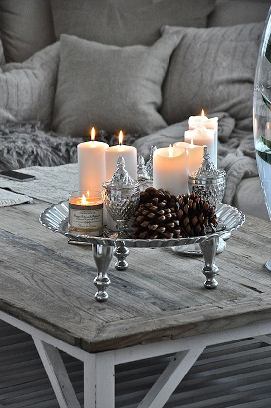 Grey and silver winter interior decor with candles & pine cones.