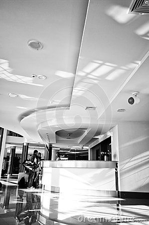 Black and white image of a modern hotel reception desk and two people checking in. Hotel interior abstract.