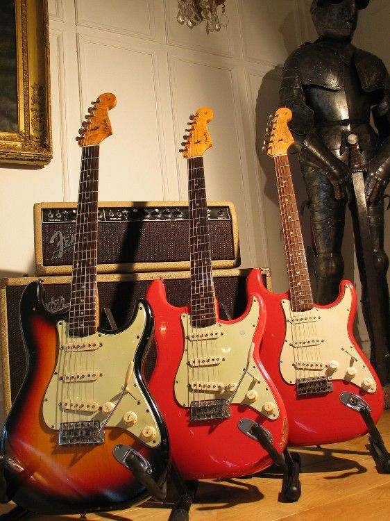 Three 60s Fender Strats, a 1963 Sunburst, a 1963 Fiesta Red and a 1964 Fiesta Red. Behind the guitars a Fender Bandmaster amp, piggyback head + cab. SInce the tolex is blonde instead of black, it maybe a 1964 transitional model, featuring blackface panel but the old cream covering of the blonde Fender era. This are from Phil Brodie's collection, http://www.philbrodieband.com/philbrodie_guitarcollection%20.htm