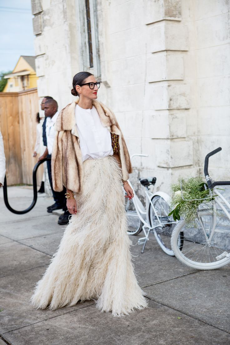 Jenna Lyons in a white button-up, full-length feather skirt, fur jacket, leopard-print clutch, and gold jewelry at Solange Knowles' wedding.