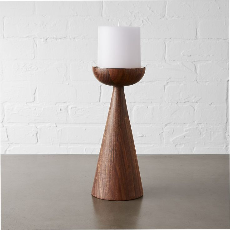 Shop baltic large pillar candle holder.   Dark wood and luxe copper combine to create a sculptural footing for the glow of a single pillar candle.  Hand-turned shesham wood is topped with a cap of copper reflecting warm light and a modern sensibility.