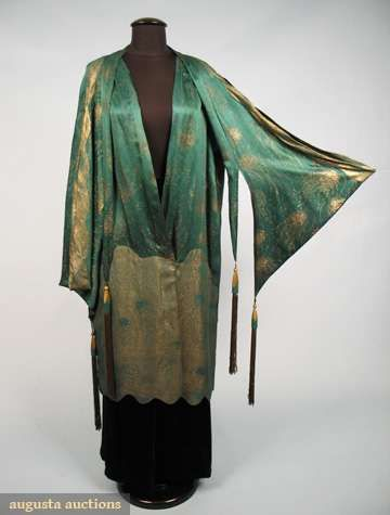 Emerald gold lame evening coat, 1920s, Scalloped inserts of reversed dotted sprays: emerald green silk satin against gold lamé & gold against green, vest-like cape w/ silk bound armhole, pagoda style over-sleeve w/ deco carved wood drops & long gold fringe, 1 hook & hand bound eyelet at centefront drop waist, intricate scalloped piecing, possibly Jeanne Lanvin