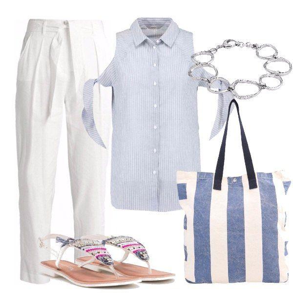Outfit composto da pantalone di lino bianco con cintura in vita, camicia a righe con fiocchi sulle braccia, infradito bianco con applicazioni colorate, shopping bag a righe e braccialetto argentato.