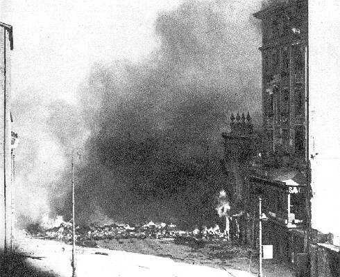 """I climb onto the roof of a house in the New World. I see the intersection of Nowy Swiat and Ordynacka Warecka, burning barricade. Great contrast of the image - strong autumn sun, white walls and black smoke. Negative very"""" dense """"because it exposed for the shadows"""