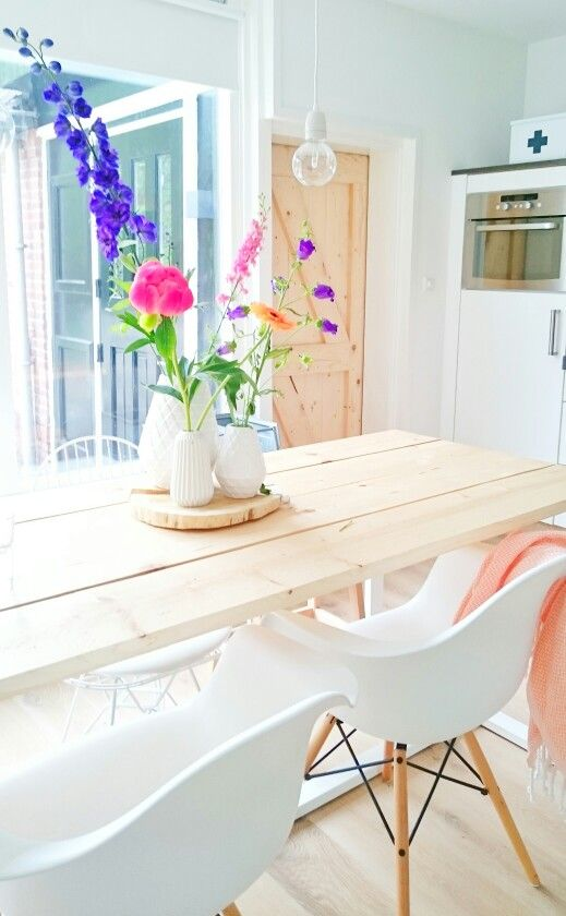 Love that it is so light! (White and wood). Love the light wooden table and the awesome flowers that really make this room pop