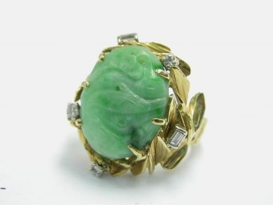 One 18 karat yellow gold handcrafted ring with a bark textured band. One carved and pierced jadeite jade of light green colour with deeper tones. Two straight baguette cut diamonds (0.12 carats VS/SI clarity: F-G-H colour). Three round brilliant cut diamonds (0.16 carats: VS/SI clarity: F-G-H colour).