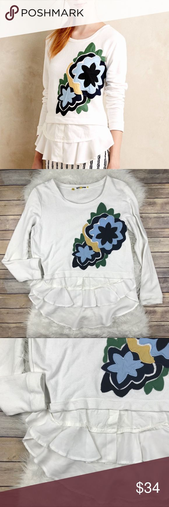 """Anthropologie Rosalie Tiered Appliqué Sweatshirt Good condition Anthropologie Little Yellow Button Rosalie Tiered Appliqué Sweatshirt. Size Medium. Stain on cuff, light wash wear. Shirttail hem peeks out from under a floral Appliqué Sweatshirt. 87% cotton, 13% polyester. Bust 43"""", length at front 26"""", length at back 30.5"""", sleeve length 25"""". White. High/low hemline. No trades, offers welcome. Anthropologie Tops Sweatshirts & Hoodies"""
