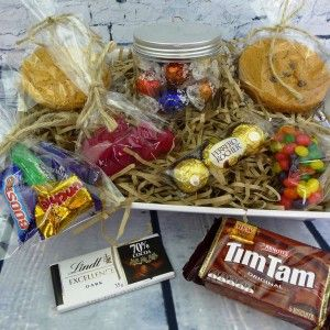 """This hamper includes two bags of yummy lollies, a jar of luxury belgian chocolates, two scrummy jumbo cookies, a pack of Ferrero Rocher, a packet of classic australian Tim-Tams, a bar of dark chocolate and a bag of """"favourites"""".  http://littlepressie.com.au/store/ultimate-goody-hamper/"""