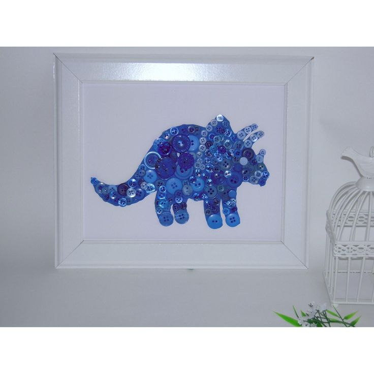 This dinosaur has been made using a variety of blue buttons that have been glued to white card and mounted in a white frame. The frame measures 25cm x 30cm and is ready for hanging. It would look beautiful in any little boys room.Other colours can be made on request ****Not suitable for children under 3 as it has small parts unless kept out of reach****