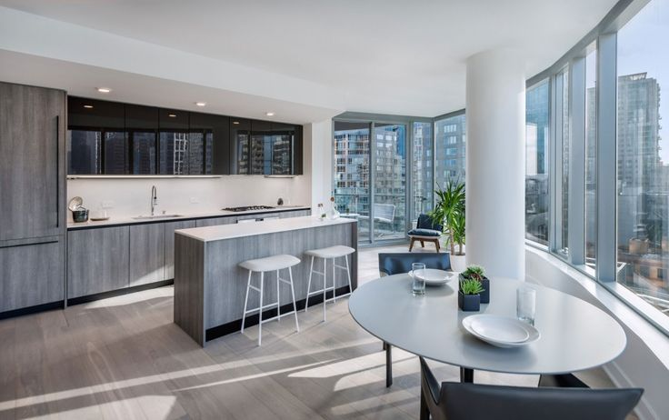 Waterfront San Francisco city views reflected in dark, glossy SieMatic cabinetry and paired with the natural look of a grey-toned veneer in the Lumina building